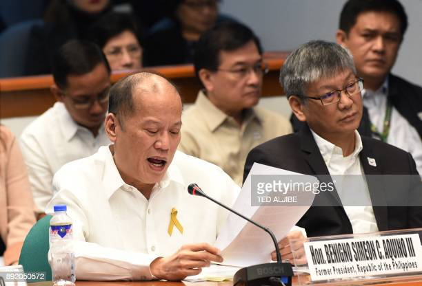 Former Philippine president Benigno Aquino reads his statement while former executive secretary Paquito Ochoa listens during the continuing hearing...