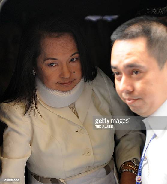 Former Philippine president Gloria Arroyo is helped by her son legislator Dato Arroyo to disembark from a vehicle as she arrives to appear in court...