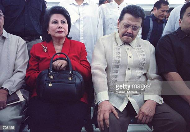 Former Philippine President Joseph Estrada flanked by his wife Luisa and son Jose Victor grimaces while waiting for a court hearing to start in his...