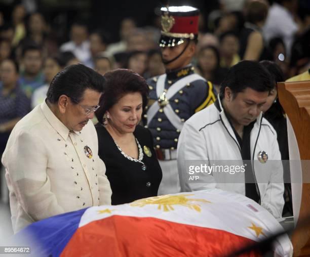 Former Philippine president Joseph Estrada his wife Luisa Estrada and his son Senator Jinggoy Estrada pay their respects in front of the coffin...