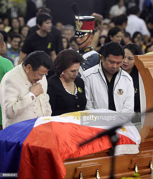 Former Philippine president Joseph Estrada pays his last respects with wife Luisa Estrada and his son Senator Jinggoy Estrada in front of the coffin...
