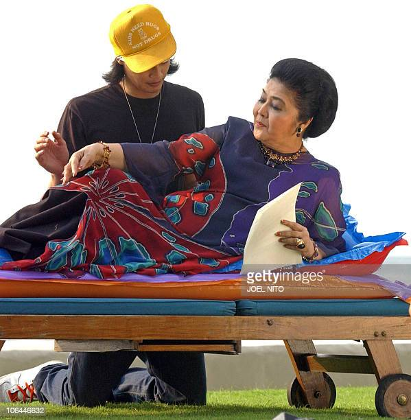 Former Philippines first lady Imelda Marcos is assisted by her grandson Martin Borgy Manotoc for a photo shoot beside the bayside pool of a top hotel...