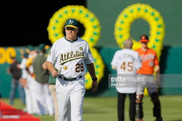 Former pitcher and current coach Curt Young of the 1989 Oakland A's carries a rose in remembrance of Bob Welch, who died June 9, joins his teammates...