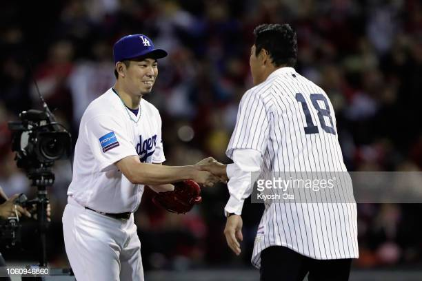 Former pitcher Hiroki Kuroda shakes hands with Pitcher Kenta Maeda of the Los Angeles Dodgers after throwing a ceremonial first pitch prior to the...