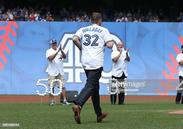 Former pitcher Roy Halladay of the Toronto Blue Jays is introduced as Tom Henke and Duane Ward applaud during the fortieth season celebrations...