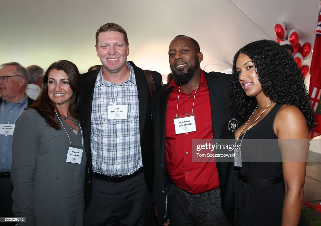 Former pitcher Roy Halladay of the Toronto Blue Jays poses with his wife Brandy Halladay as former player Vladimir Guerrero of the Montreal Expos poses with his girlfriend Roxanne Rodriguez after being honored during the induction ceremony at the Canadian Baseball Hall of Fame on June 24, 2017 in St Marys, Canada.