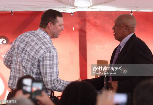 Former pitcher Roy Halladay of the Toronto Blue Jays receives a jacket from former pitcher Ferguson Jenkins as he is honored during the induction...