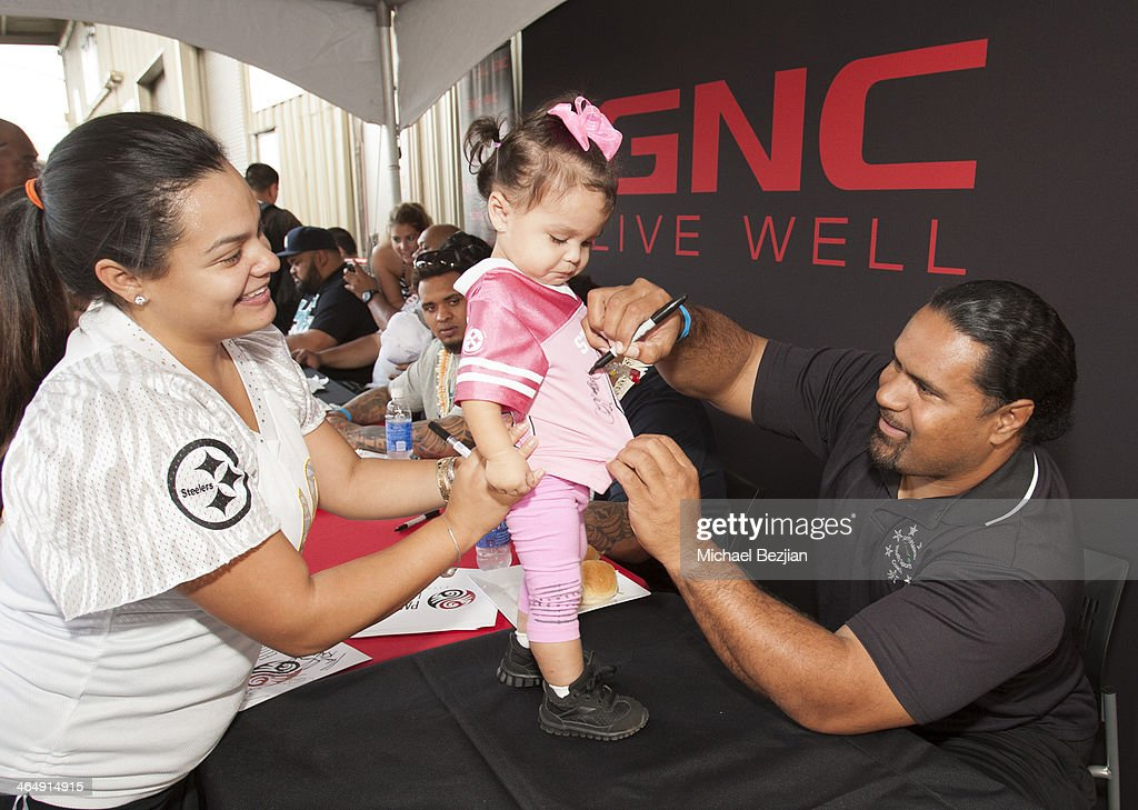 Former Pittsburg Steeler Chris Fuamatu-Ma'afala signs his autograph on a young fan's jersey at the Pacific Elite Sports Fitness Center Grand Opening on January 24, 2014 in Kaneohe, Hawaii.