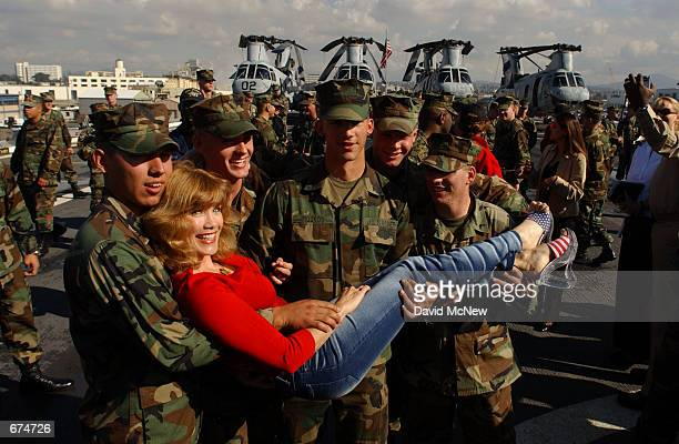Former Playboy model Barbie Benton poses with Marines and Sailors aboard the USS Ogden November 30 2001 at the 32nd Street Naval Station in San Diego...