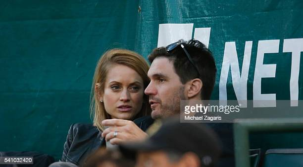 Former player and current song writer Barry Zito watches the game between the Detroit Tigers and the Oakland Athletics, with his wife Ambee, at the...