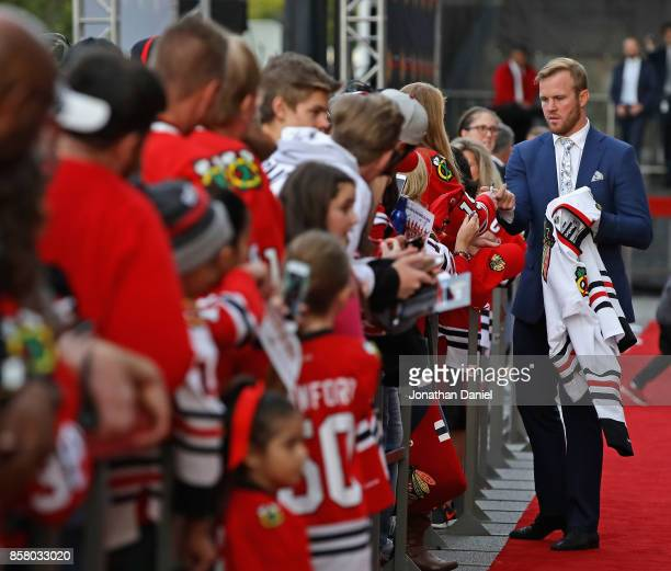 Former player Brian Bickell of the Chicago Blackhawks who signed a one day contract to retire as a member of the Blackhawks stops to sign an...