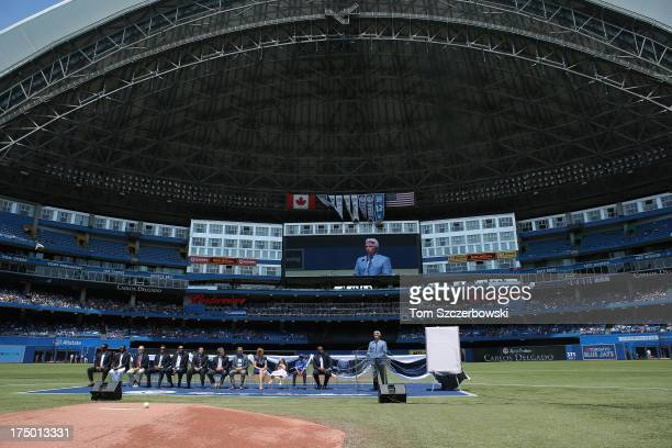 Former player Carlos Delgado of the Toronto Blue Jays sits with his wife and two kids as he is honored in a pregame ceremony placing his name on The...