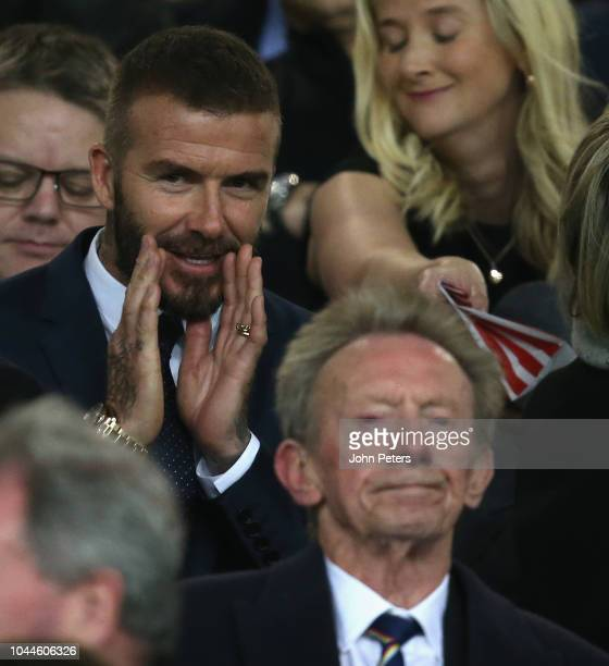 Former player David Beckham shouts at Denis Law in the director's box ahead of the UEFA Champions League between Manchester United and Valencia at...