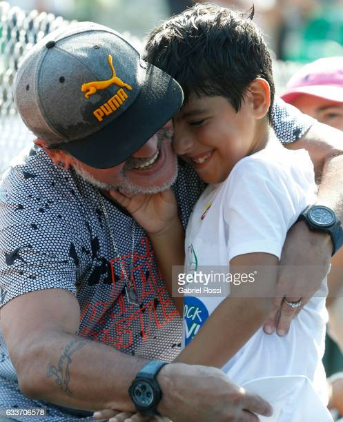 Former player Diego Maradona with his grandchild Benjamin Aguero are seen during a singles match between Carlos Berlocq and Andreas Seppi as part day...