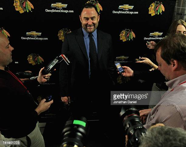 Former player Ed Belfour of the Chicago Blackhawks meets in the hallway with reporters before being honored on the ice by the Blackhawks organization...