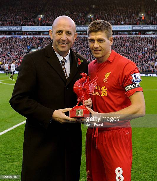 Former player Gary McAllister presents Liverpool captain Steven Gerrard with a trophy in honour of his 600th appearance for the club before the...