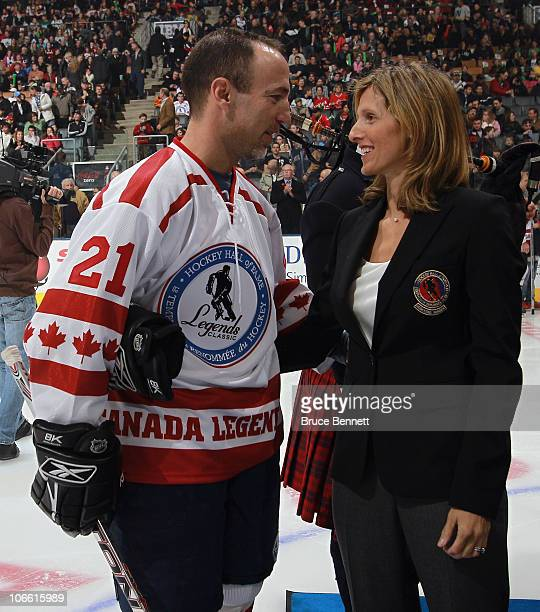 Former player Ray Ferraro and husband of Cammi Granato speaks with her following the Hockey Hall of Fame blazer ceremony prior to the Legends Classic...