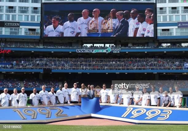 Former players and coaches pose for a group photo in a ceremony before the game honoring the 25th anniversary of the clubs backtoback World Series...