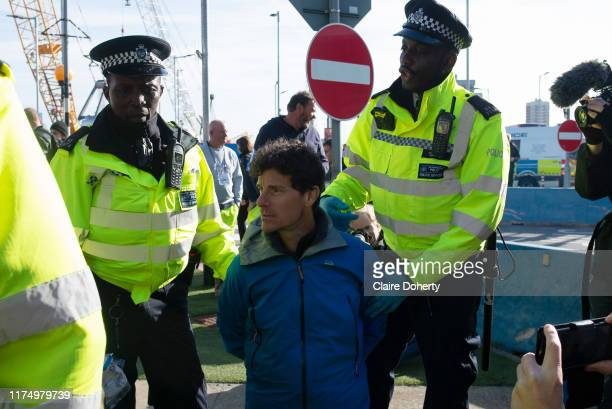 Former police officer John Curren age 49, is arrested as climate change protest group Extinction Rebellion stage a protest at London City Airport...