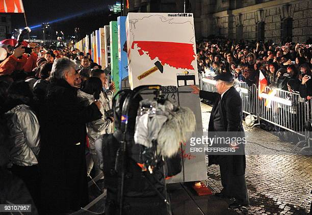 Former Polish President Lech Walesa pushes the first of the individually painted dominos along the former route of the wall in front of the Reichstag...