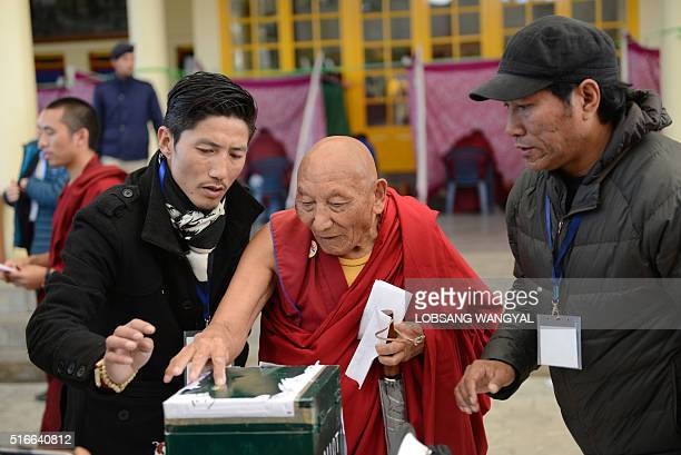 Former political prisoner 85yearold Tibetan Palden Gyatso is guided as he casts his vote to elect a Sikyong of the Central Tibetan Administration and...