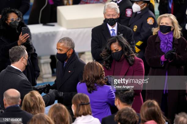 Former President Barack Obama greets Doug Emhoff as Vice President Elect Kamala Harris greets former First Lady Michelle Obama as former President...