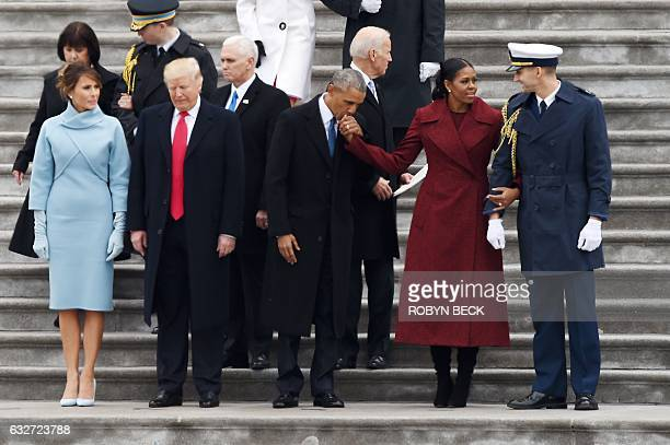 Former President Barack Obama kisses the hand of former First Lady Michelle Obama beside US President Donald Trump and First Lady Melania Trump...