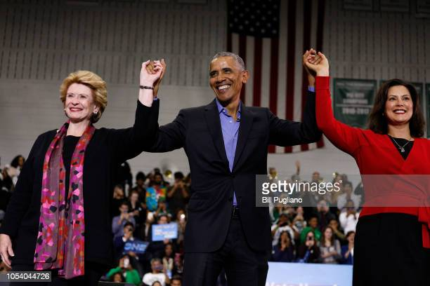 Former President Barack Obama raises his arms with Michigan Senator Debbie Stabenow and Michigan gubernatorial candidate Gretchen Whitmer at a rally...