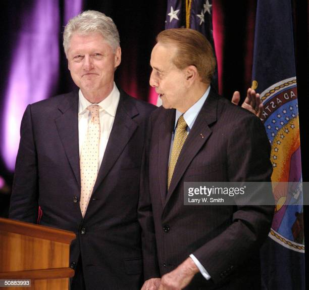 Former President Bill Clinton gives former Senator Bob Dole a pat on the back as Dole introduces him before Clinton was to give the inaugural Dole...