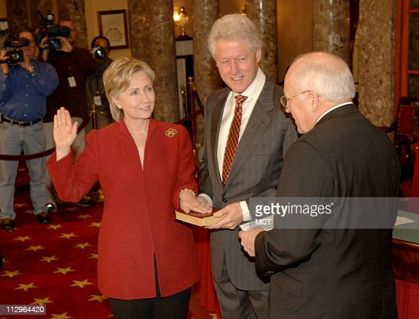 Former President Bill Clinton holds the Bible as his wife Sen Hillary Rodham Clinton reenacts her Senate swearingin with VicePresident Dick Cheney...