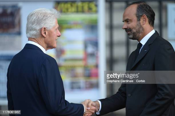 Former President Bill Clinton is greeted by France's Prime Minister Edouard Philippe as he arrives to attend a church service for former French...