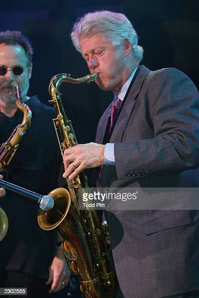 Former President Bill Clinton performs a saxaphone solo to The Blues Brothers version of I saw her standing there by The Beatles during the opening...