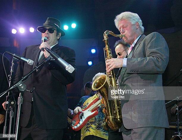 Former President Bill Clinton performs a saxaphone solo with Dan Aykroyd of The Blues Brothers during the opening of the new Mohegan Sun resort and...