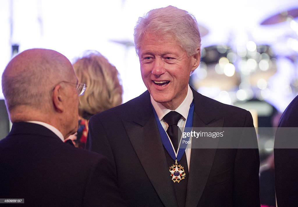 Former President Bill Clinton talks to a guest during a dinner in honor of the Medal of Freedom awardees at the Smithsonian National Museum of American History on November 20, 2013 in Washington, DC. The Presidential Medal of Freedom is the nation's highest civilian honor, presented to individuals who have made meritorious contributions to the security or national interests of the United States, to world peace, or to cultural or other significant public or private endeavors.