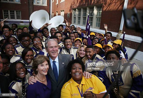 Former President George Bush and former First Lady Laura Bush take a selfie photo with Asia Muhaimin the Warren Easton High School band director and...