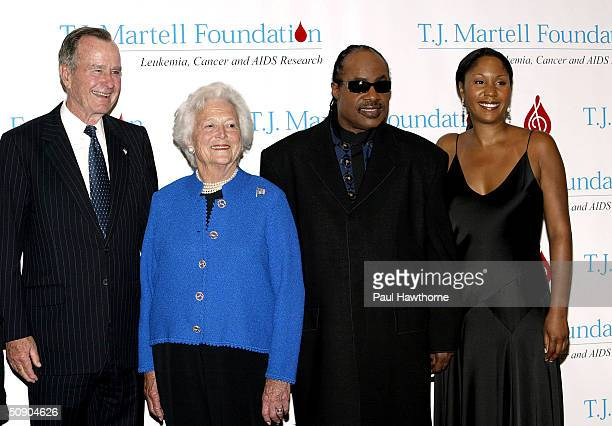 Former President George H W Bush and his wife Barbara along with singer Stevie Wonder and his daughter Aisha Morris pose for photographers before the...