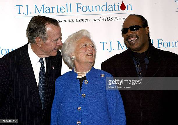 Former President George H W Bush and his wife Barbara talk with Singer Stevie Wonder as they pose for photographers before the start of the 29th...