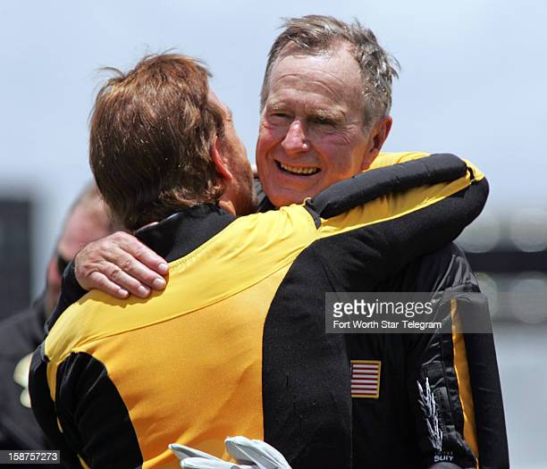 Former President George H W Bush hugs actor Chuck Norris after his parachute jump in celebration of his 80th birthday in College Station Texas on...