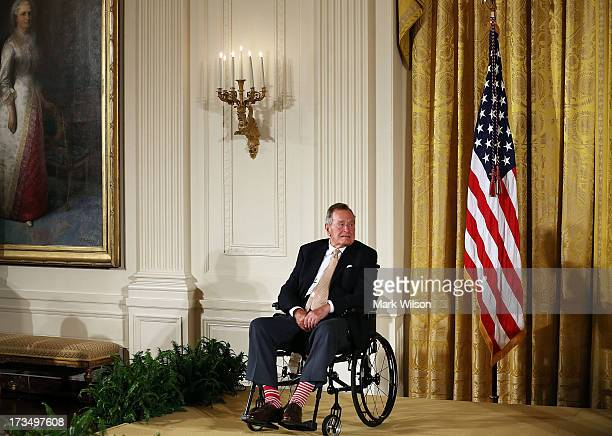 Former President George H W Bush sits in a wheelchair during an event in the East Room at the White House July 15 2013 in Washington DC Bush joined...