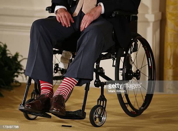Former President George H W Bush wears red stripped socks as he sits in a wheelchair during an event in the East Room at the White House July 15 2013...