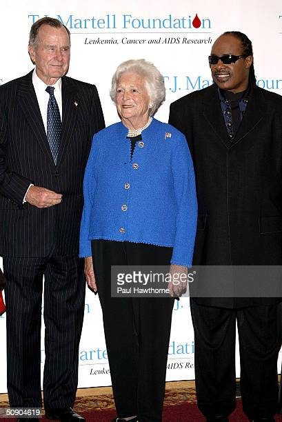 Former President George H W Bush with his wife Barbara and Singer Stevie Wonder pose for photographers before the start of the 29th Annual TJ Martell...