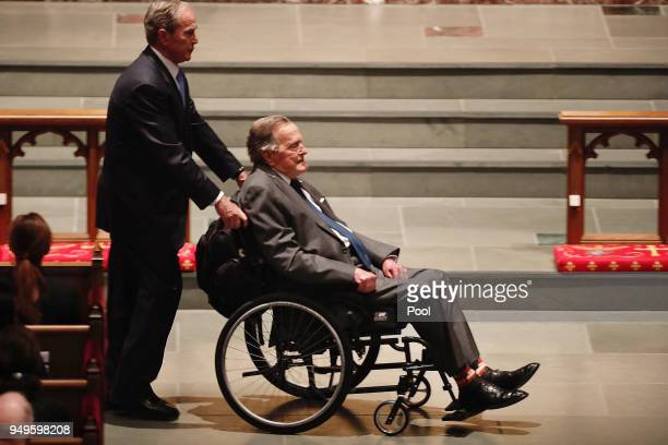 Former President George HW Bush assisted by his son former President George W Bush enter the church during the funeral for former First Lady Barbara...