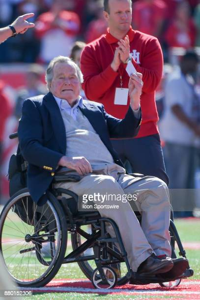 Former President George HW Bush prepares for the coin toss before the football game between the Navy Midshipmen and Houston Cougars on November 24...