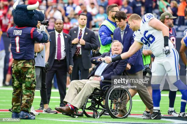 Former President George HW Bush shakes hands with Indianapolis Colts defensive tackle Henry Anderson before the coin toss at midfield before the...