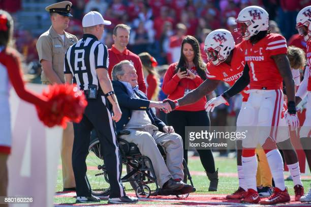 Former President George HW Bush shakes hands with the captains for each team after the coin toss before the football game between the Navy Midshipmen...