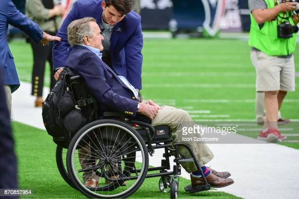 Former President George HW Bush watches the flag unfurl at midfield prior to the coin toss before the football game between the Indianapolis Colts...