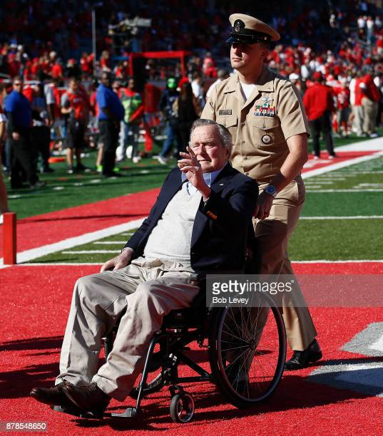 Former President George HW Bush waves to the crowd after participating in the coin flip before the game between the Navy Midshipmen and the Houston...