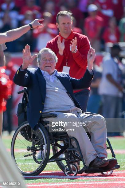Former President George HW Bush waves to the crowd before the coin toss before the football game between the Navy Midshipmen and Houston Cougars on...