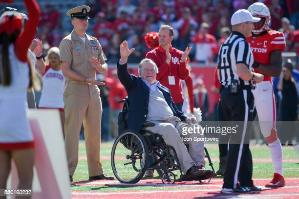 Former President George HW Bush waves to the crowd during pregame coin toss before the football game between the Navy Midshipmen and Houston Cougars...