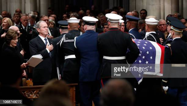 Former President George W Bush and first lady Laura Bush place their hands over their hearts as the flagdraped casket of former President George HW...